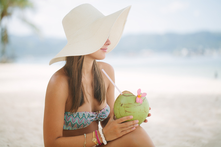 Beautiful woman relaxing on a paradise beach with coconut Banque d'images