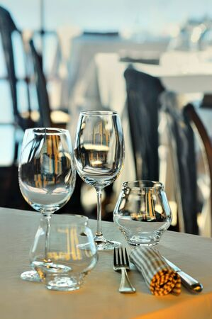 quay: Wine glasses and dishes on the summer terrace of the restaurant above the sea