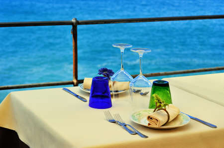 cerulean: Decorated table with a glass on the restaurant terrace by the sea