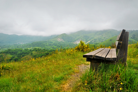 bench alone: Lonely bench on a hill with mountain scenery around