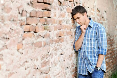 conceived: conceived young man brick wall background