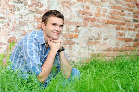 no shirt: Smiling young man on the grass near brick wall