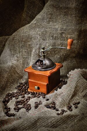 coffee grinder: Old coffee grinder with beans on brown burlap