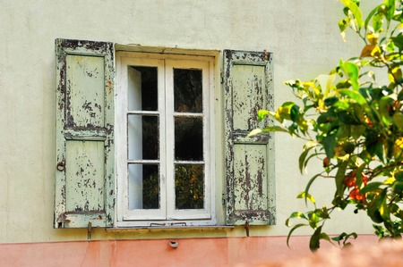 pinks: Old  scratched white window with light green shutters