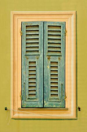 light green wall: Old green window shutters on the light green wall