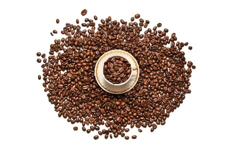 scattered on white background: A cup of coffee and coffee grains scattered on a white background Stock Photo
