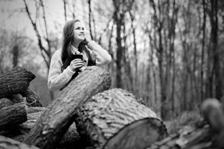 conceived: Beautiful young girl with cup of warming drink in the forest at the cold season Stock Photo