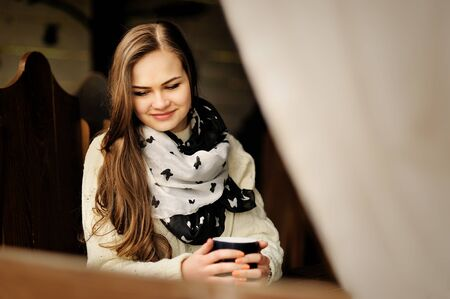arbor: pretty young girl with cup of  warming drink in the arbor at the cold season Stock Photo