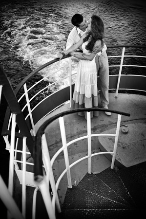 romantic couples: couple kissing on the ship deck with waves