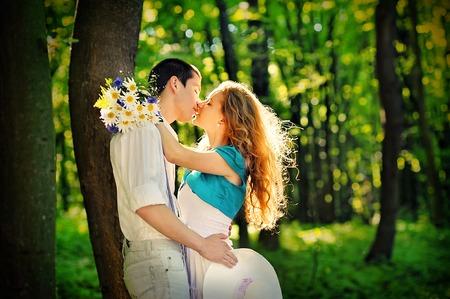 innamorati che si baciano: amanti baciare nei boschi con un mazzo di margherite