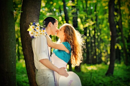 romantic date: lovers kissing in the woods with a bouquet of daisies