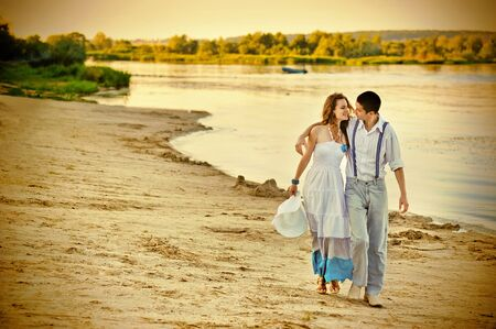 suspenders: loving couple walking along the shore at sunset