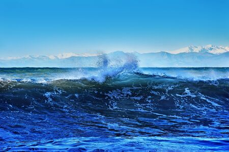 ridge of wave: wave splashes against the background of the mountains