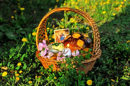 Easter basket on the grass with dandelion background Stock Photo