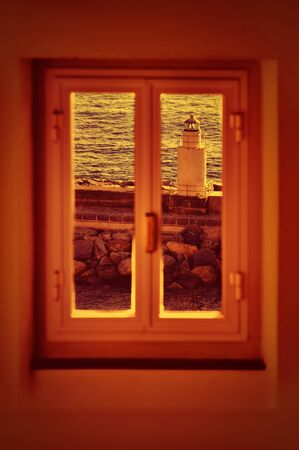 through: lighthouse sunset view through window