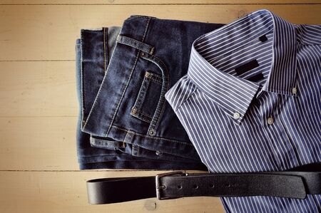 decomposed: Mens jeans, shirt and belt decomposed on a wooden background