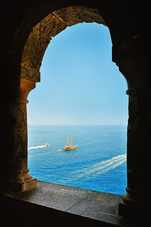 middle ages boat: arcade window and view of the sea with yacht