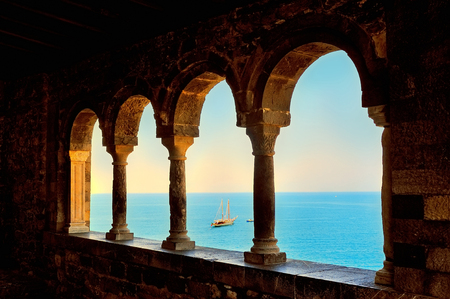 middle ages boat: arcade windows with columns and view of the sea at sunset Stock Photo