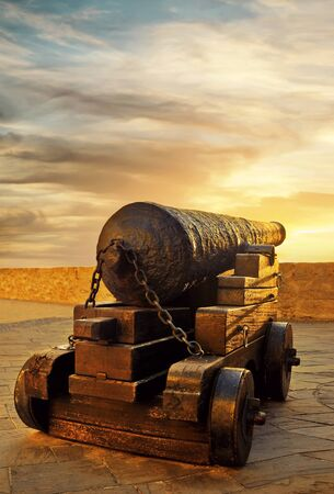 nuclei: old pirate gun on nuclei at sunset Stock Photo