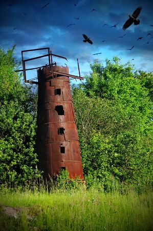 mysticism: mysticism rusty water tower with crows Stock Photo