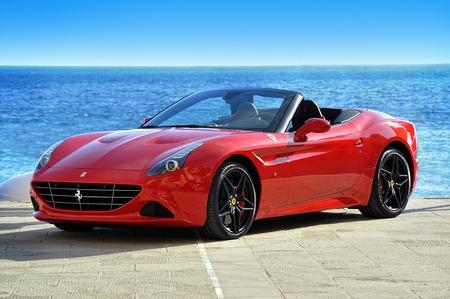 Rosso Ferrari California T Handling Speciale sul lungomare del Mar Mediterraneo a Camogli, foto catturata in un ambiente urbano Camogli, Liguria, Italia Archivio Fotografico - 56054854