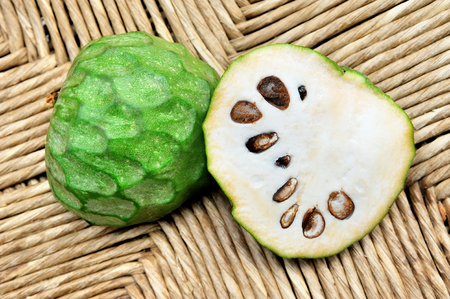 chirimoya: green fruit cherimoya cut on natural Woven background Stock Photo
