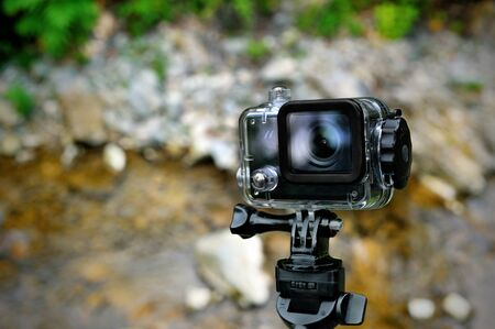 cam gear: Action waterproof camera on mountain river background