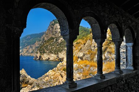 middle ages: Middle Ages arcade with columns and view on mountains with sea Stock Photo