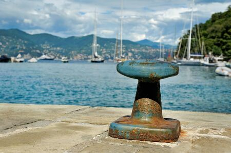 mooring: Mooring post in Portofino harbor with yachts cloudly sky background Stock Photo