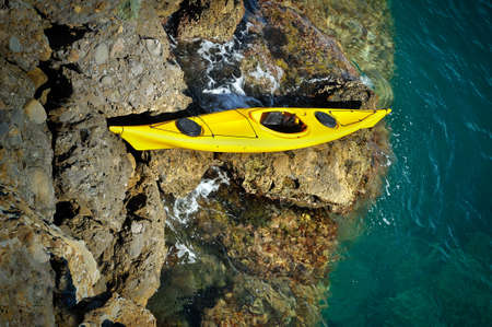 beached: yellow sea kayak beached on a rocky rapids and blue water