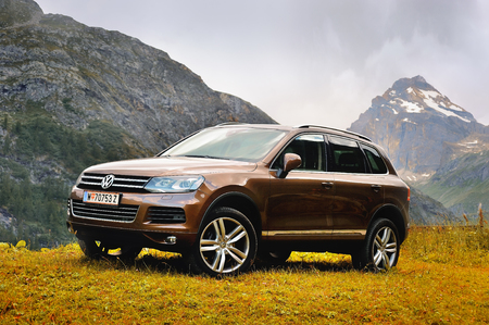 Showy Volkswagen Touareg in alps with background view of Granta Parey mountain, Valle dAosta, Italy