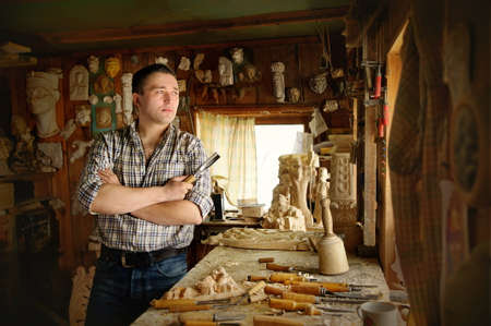 trinchante: Portrait of young carver in workshop with woodworking Equipment