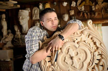 trinchante: Portrait of young carver in workshop with woodworking