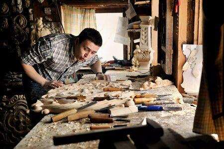 carver: Carver in workshop of wood carving blow off sawdust Editorial