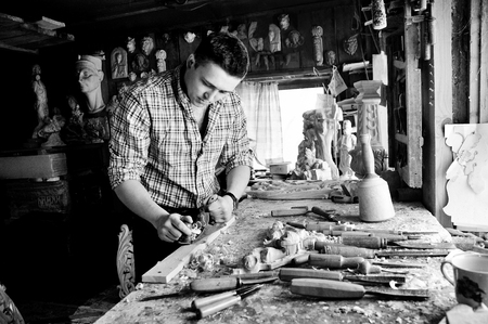 carver: carver in workshop carving with chisel monochrome