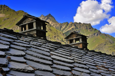 stoned: alpien stoned roof with chimneys in mountains