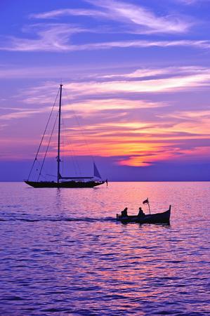 pez vela: cielo púrpura bajo el mar con el barco y barco de vela silueta Foto de archivo