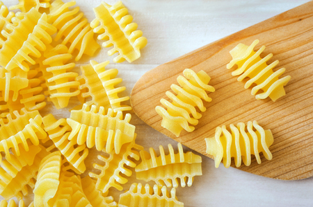 tube top: closeup of pasta lying with wooden spoon on white table. Stock Photo