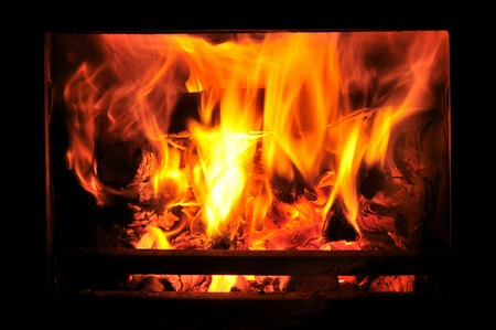 woodburner: Wood burning stove with fire in window Stock Photo