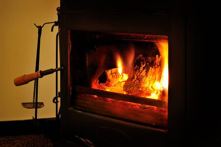 woodburner: Wood burning stove with fire and poker Stock Photo