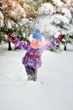 little Caucasian girl tossing snow in rainbow Stock Photo