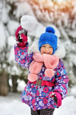 palle di neve: Little happy girl with a scarf playing snowballs