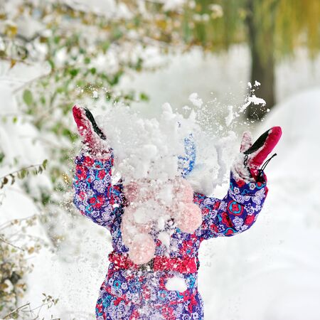 winterday: Happy Girl throws snow raised her hands up Stock Photo