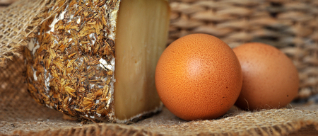 sectioned: Sbarro cheese with grain encrusted surface on rural burlap with eggs Stock Photo