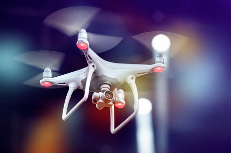 quadrocopter - the new technology is flying on evening ligts background