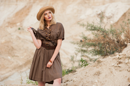 girl in a khaki dress in a safari style and hat on sand background