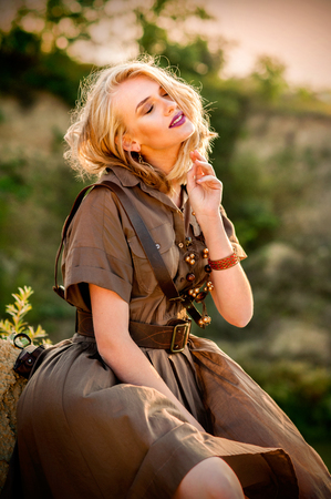 Pretty blonde girl in safari summer dress sitting on the sand with scattered hair Reklamní fotografie