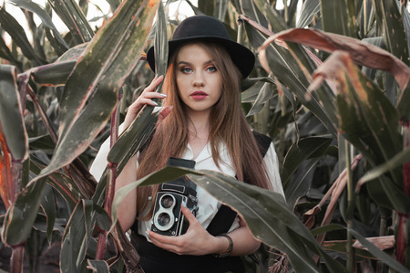 Young girl portrait and retro camera and old fashion style clothing in corn field Stock Photo