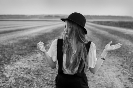 Old fashioned girl with suspenders and hat, wolk on field at sunset time Stock Photo