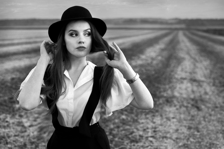 An old-fashioned girl with a suspender and a hat, walking in the field Stock Photo